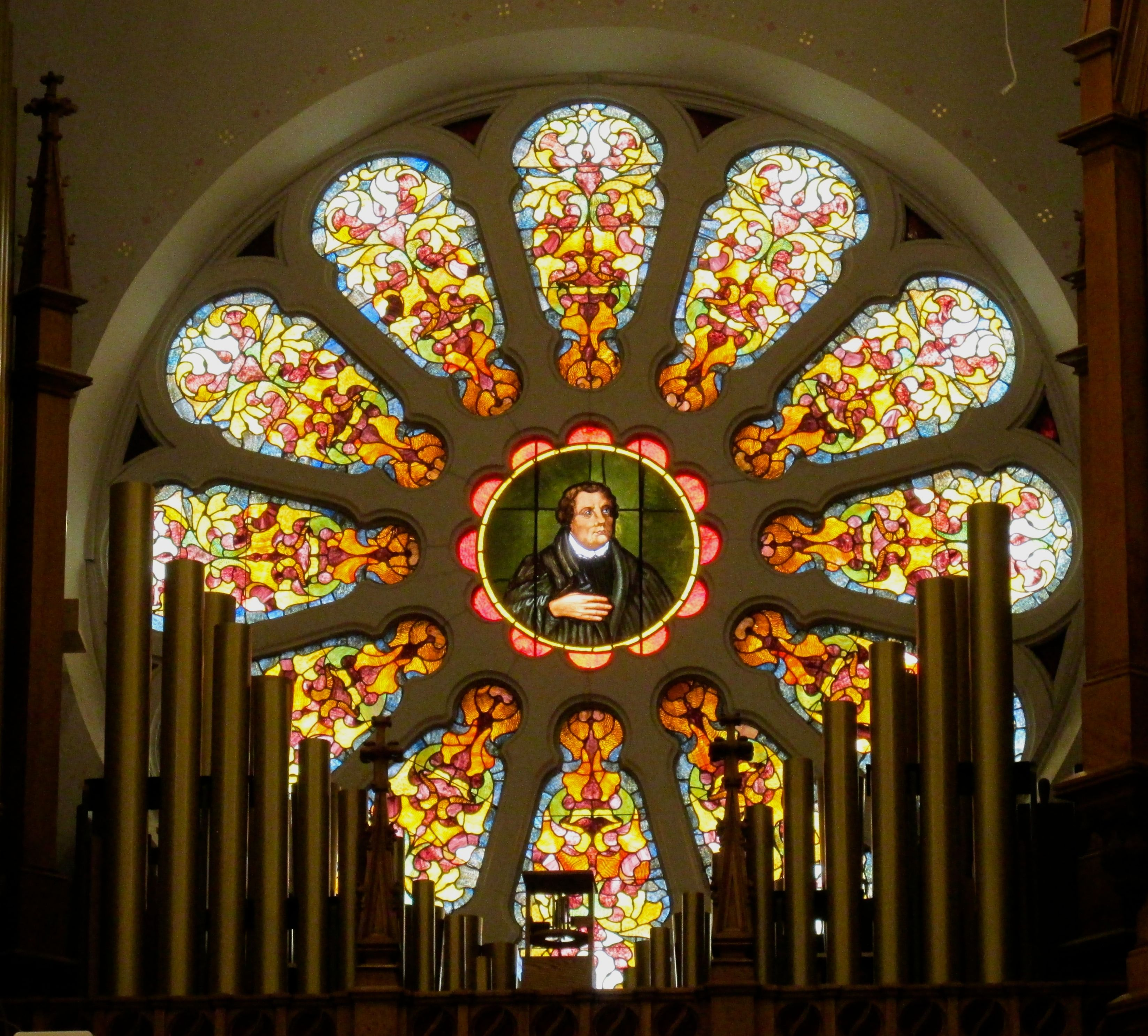 Rose window in the organ loft with Martin Luther's portrait
